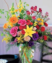 Alstroemeria, roses, chrysanthemums, gerberas, and snapdragons in a glass vase.