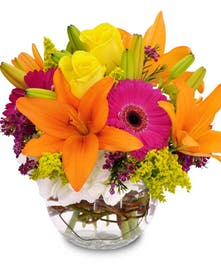 Orange lilies, pink daisies and other bright flowers in a glass bowl vase.