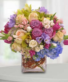 Pastel orchids and hydrangea in a clear glass vase.