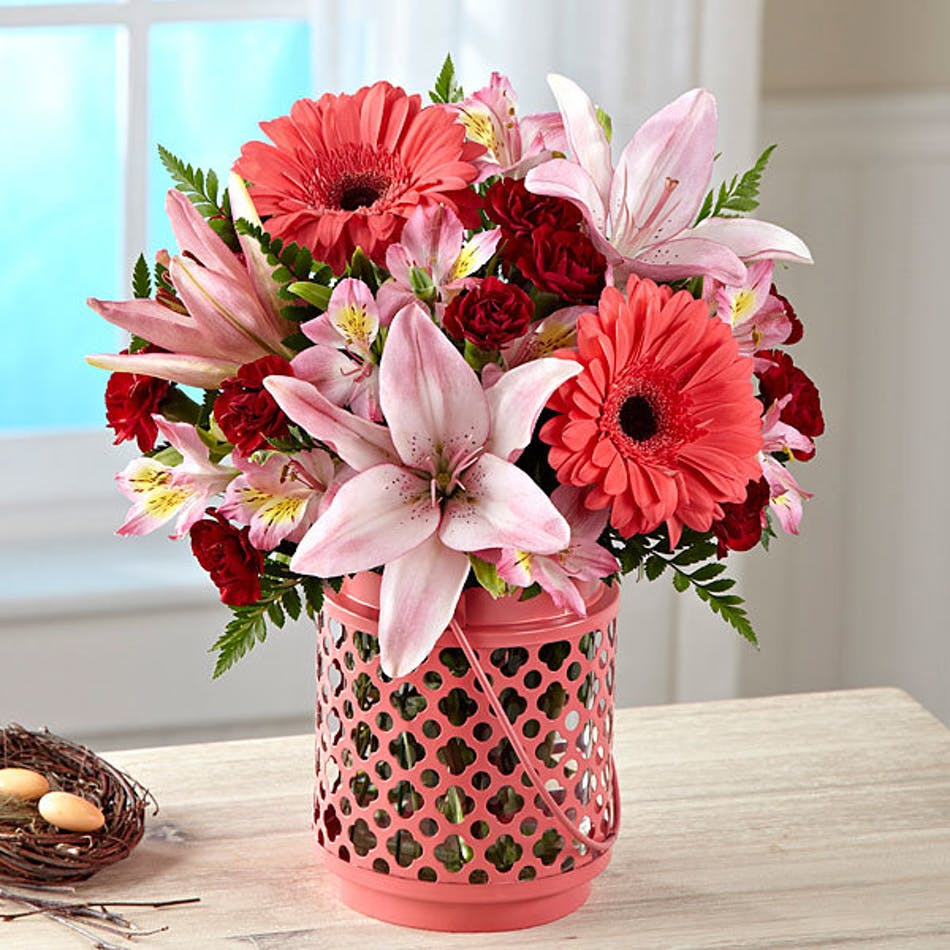 Pink and red flowers in a pink lantern style vase.