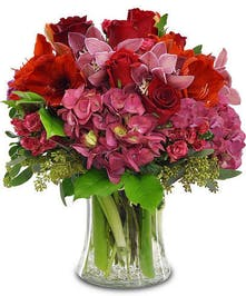 Premium hydrangea, roses, orchids and more in a clear glass vase.