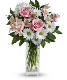 Pink and white daisies, roses and alstromeria lilies in a clear vase.
