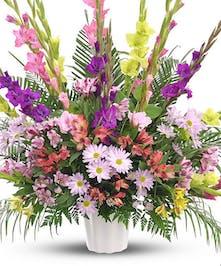 Floor basket presentation of pink, purple and yellow blooms.