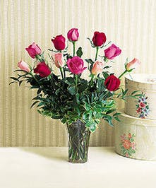 Roses in assorted colors arranged in a glass vase with greenery and baby's breath.