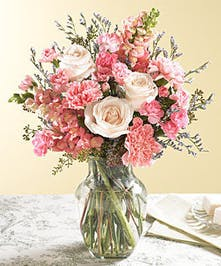 Pink roses, snapdragons and carnation flowers in a vase.