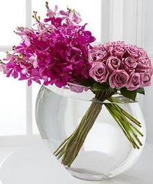 Roses and orchids in a glass bowl vase.