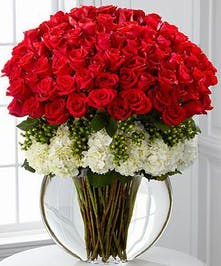 24 Long-stem red roses and white hydrangea flowers with green hypericum berries in a glass vase.