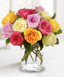 Twelve mixed color roses with greenery arranged in a rectangular vase.