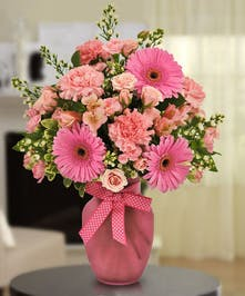 Pink vase of roses, carnations and gerbera daisies tied with a pink bow.
