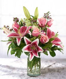 Roses, stargazer lilies and Queen Anne's lace bouquet in a glass vase.