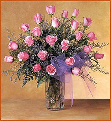 Two dozen pink roses and baby's breath in a clear glass vase.