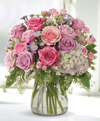 Hydrangea and roses in a clear glass vase.