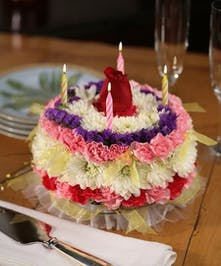 Birthday cake made entirely of flowers in white, purple and pink with 4 lit birthday candles on top.