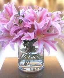 Clear glass vase filled with pink stargazer lilies.