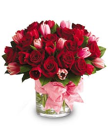 Red and pink bouquet of roses and tulips in a glass cylinder vase tied with pink ribbon.