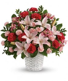 Basket of pink lilies, red carnations and other flowers in a sympathy arrangement.