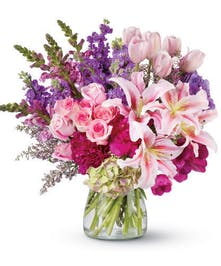Peonies, lilies, tulips and more flowers in shades of pink and purple in a clear glass vase.