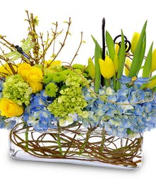 Blue hydrangea, yellow tulips and more in a long glass cube vase.
