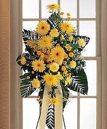 Bright yellow sympathy spray accented with greenery.
