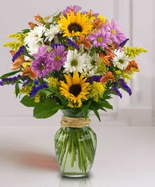 Sunflowers and other mixed flowers in a glass vase.