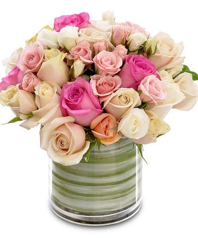Roses of various colors arranged in a bubble bowl vase.