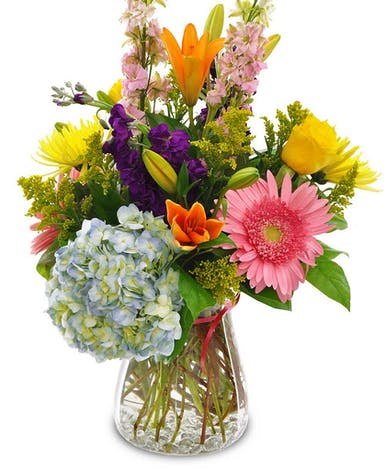 Assorted flowers in a clear glass vase.