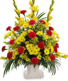 Bright yellow and red flowers in a sympathy presentation.