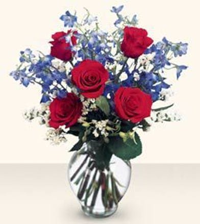 Red roses, blue belladonna, and white statice in a clear glass vase.