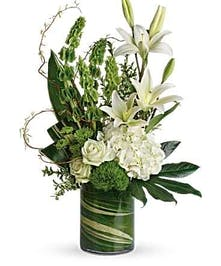 Leaf-lined cylinder vase filled with white hydrangea and lilies with greenery.