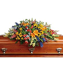 Bright and colorful cakset spray of hydrangea, roses, lilies, sunflowers and more.
