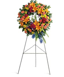 Bright wreath of green, hot pink, orange, blue, yellow and purple flowers accented with greenery.