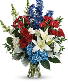 Patriotic tribute bouquet of red, white and blue flowers.