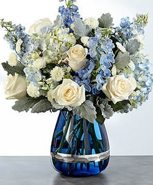 Blue and white roses and hydrangea flowers in a blue glass vase.