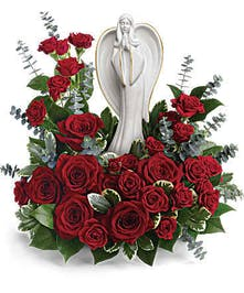 Porcelain angel sculpture keepsake surrounded by red roses and greenery.