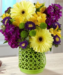Yellow, purple and green flowers in a green lantern style vase.