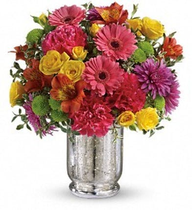 Pink, yellow and purple flowers in a mercury glass hurricane.