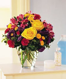 Alstroemeria, asters, carnations and chrysanthemums in a clear glass vase.