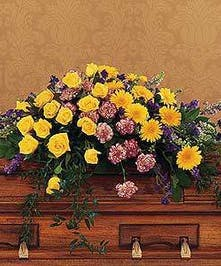 Casket spray of yellow and purple flowers with greenery.