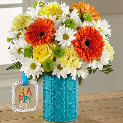 Bright flowers in a teal vase.
