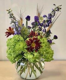 Green hydrangea, safari sunset, blue delphinium and more in a glass bowl vase.
