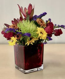 Red cube vase filled with autumn flowers.