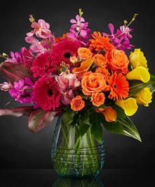 Red, yellow, orange and pink flowers in a clear glass vase.