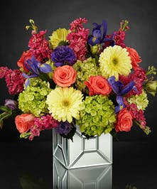 Mirrored cube vase of purple, green, coral and yellow flowers.