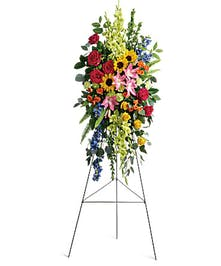 Floral sympathy spray of bold and bright flowers.