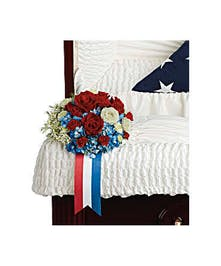 Casket pillow of blue hydrangea and red and white roses with a patriotic ribbon.