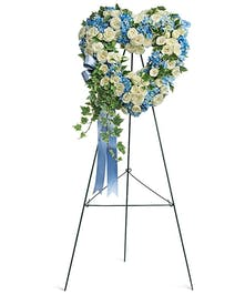 Heart-shaped wreath of light blue and white flowers accented with blue ribbon.