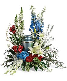Patriotic urn arrangement of blue hydrangea, white orchids and red roses.