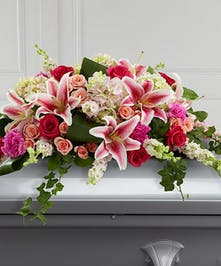 Casket spray of roses, carnations, lilies and hydrangea with greenery.