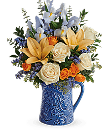 Crème roses, orange spray roses, peach asiatic lilies, light blue iris, and blue sinuata statice  in a blue pitcher vase.