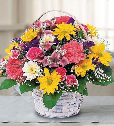 Yellow, pink and purple flowers in a white handbasket.